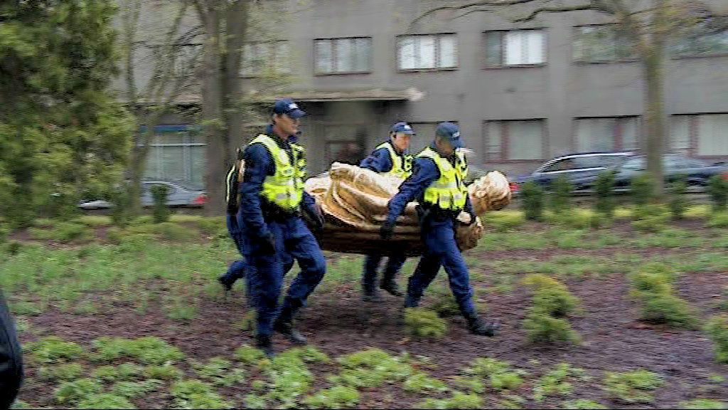 Fig 3 Still from video of Kristina Norman's intervention in public space 2009, soldiers remove the golden replica © Kristina Norman 2009